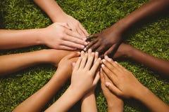 Enfants gardant des mains ensemble au-dessus de l'herbe Images libres de droits