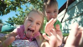 Enfants grimaçants posant sur la pelouse clips vidéos