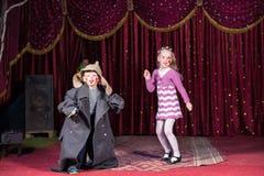 Enfants habillés comme clowns exécutant sur l'étape Photos stock