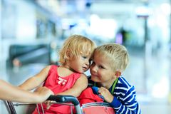 Enfants heureux à l'équitation d'aéroport sur le chariot de bagage Images stock