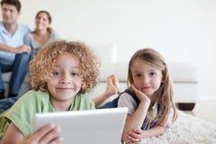 Enfants heureux à l'aide d'un ordinateur de comprimé tandis que leurs parents heureux Image libre de droits