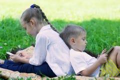 Enfants heureux à l'aide de la tablette et du smartphone Images stock