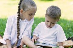 Enfants heureux à l'aide de la tablette sur l'herbe Photo stock