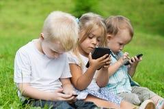 Enfants heureux à l'aide des smartphones Photo stock