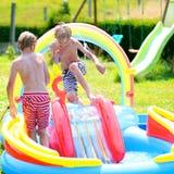 Enfants heureux éclaboussant dans la piscine gonflable de jardin photo stock