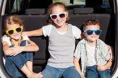Enfants heureux étant prêts pour le voyage par la route un jour ensoleillé Images stock