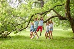 Enfants heureux accrochant sur l'arbre en parc d'été Image libre de droits