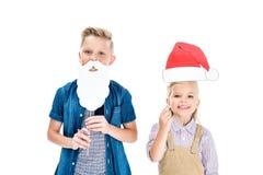 enfants heureux adorables avec le chapeau de Santa et la barbe de faux souriant à l'appareil-photo Image libre de droits