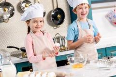 enfants heureux adorables dans des chapeaux de chef et tabliers souriant à l'appareil-photo tout en faisant la pâte ensemble Images stock