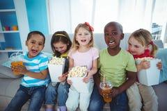 Enfants heureux appréciant le maïs éclaté et les boissons tout en se reposant Photo libre de droits