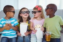 Enfants heureux appréciant le maïs éclaté et les boissons tout en se reposant Photos libres de droits