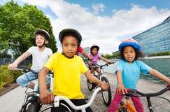 Enfants heureux appréciant montant des bicyclettes en été Image libre de droits
