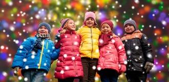 Enfants heureux au-dessus des lumières de neige et de Noël Photographie stock