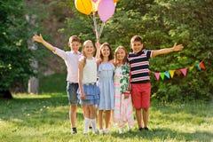 Enfants heureux avec des ballons à la fête d'anniversaire d'été Photographie stock libre de droits