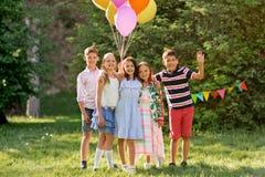 Enfants heureux avec des ballons à la fête d'anniversaire d'été Photo stock