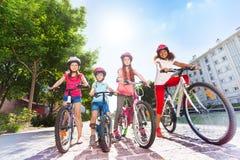 Enfants heureux avec des bicyclettes dans la ville d'été Images stock