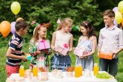 Enfants heureux avec des cadeaux sur la fête d'anniversaire à l'été Photographie stock libre de droits