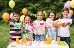 Enfants heureux avec des cadeaux sur la fête d'anniversaire à l'été Photos libres de droits