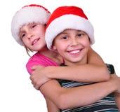 Enfants heureux avec des chapeaux de rouge de Santa Claus Photographie stock libre de droits