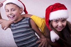 Enfants heureux avec des chapeaux de rouge de Santa Claus Photographie stock