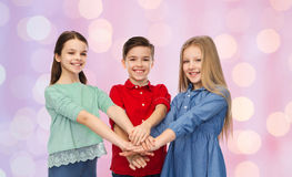 Enfants heureux avec des mains sur le dessus Image libre de droits
