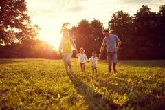 Enfants heureux avec des parents courant en parc Images libres de droits