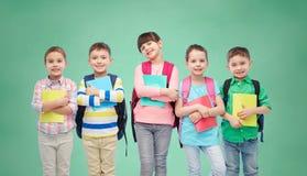 Enfants heureux avec des sacs et des carnets d'école Photo libre de droits