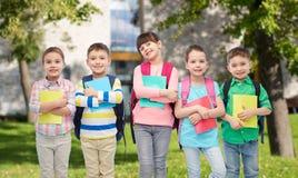 Enfants heureux avec des sacs et des carnets d'école Image libre de droits