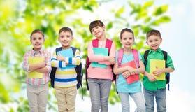 Enfants heureux avec des sacs et des carnets d'école Photo stock