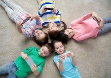 Enfants heureux avec des smartphones se trouvant sur le plancher Photos stock
