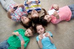 Enfants heureux avec des smartphones se trouvant sur le plancher Photographie stock libre de droits