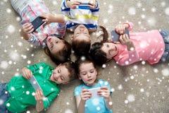 Enfants heureux avec des smartphones se trouvant sur le plancher Photographie stock