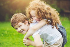 Enfants heureux avec l'équitation de ferroutage Photo libre de droits