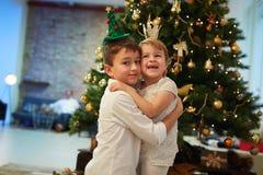 Enfants heureux avec l'arbre de Noël à la maison Photos stock