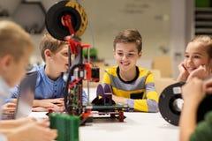 Enfants heureux avec l'imprimante 3d à l'école de robotique Image stock