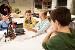 Enfants heureux avec l'imprimante 3d à l'école de robotique Images stock