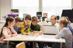 Enfants heureux avec l'ordinateur portable à l'école de robotique Photographie stock libre de droits