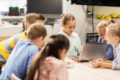 Enfants heureux avec l'ordinateur portable à l'école de robotique Photo libre de droits