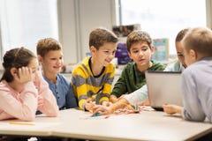 Enfants heureux avec l'ordinateur portable à l'école de robotique Image libre de droits