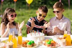 Enfants heureux avec le gâteau sur la fête d'anniversaire à l'été Image stock