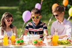 Enfants heureux avec le gâteau sur la fête d'anniversaire à l'été Photos libres de droits