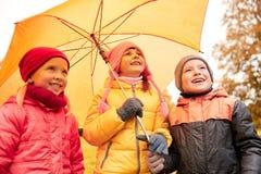 Enfants heureux avec le parapluie en parc d'automne Photos stock