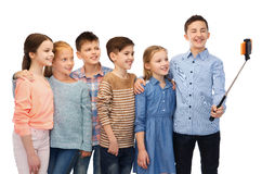 Enfants heureux avec le smartphone et le bâton de selfie Images stock