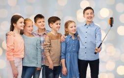 Enfants heureux avec le smartphone et le bâton de selfie Images libres de droits