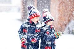 Enfants heureux ayant l'amusement avec la neige en hiver Photos libres de droits