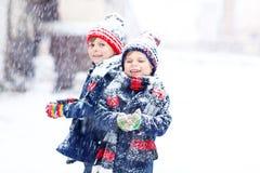 Enfants heureux ayant l'amusement avec la neige en hiver Photos stock