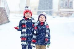 Enfants heureux ayant l'amusement avec la neige en hiver Image stock