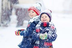 Enfants heureux ayant l'amusement avec la neige en hiver Photographie stock