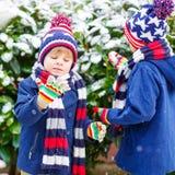 Enfants heureux ayant l'amusement avec la neige en hiver Images stock
