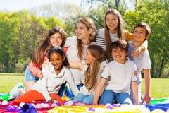 Enfants heureux ayant l'amusement se reposant sur l'herbe dans le parc Image stock